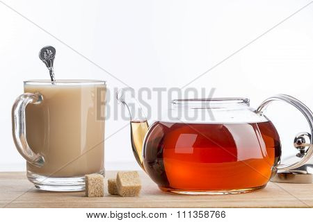 Milk dissolves in glass cup of hot tea with spoon