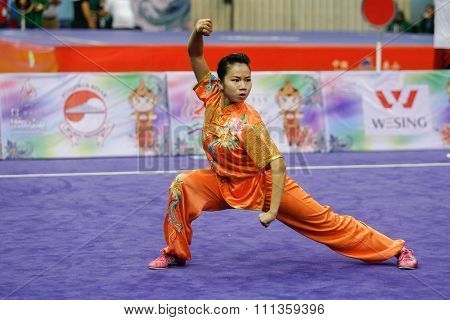 JAKARTA, INDONESIA - NOVEMBER 17, 2015: Myat Wai Phyo of Myanmar performs the movements in the women's Compulsory Changquan event at the 13th World Wushu Championship 2015 in Istora Senayan Stadium.