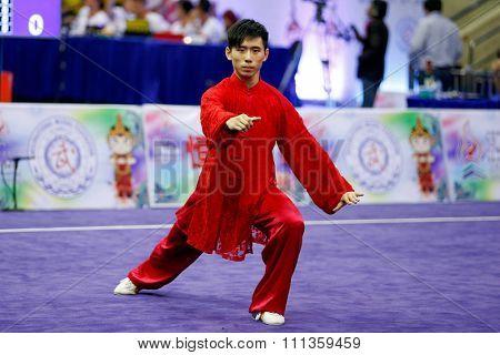 JAKARTA, INDONESIA - NOVEMBER 17, 2015: Ka Seng Chong of Macao performs the movements in the men's Compulsory Taijiquan event at the 13th World Wushu Championship 2015 at the Istora Senayan Stadium.