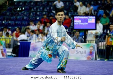 JAKARTA, INDONESIA - NOVEMBER 17, 2015: Jack Chang Loh of Malaysia performs the movements in the men's Compulsory Taijiquan event at the 13th World Wushu Championship 2015 in Istora Senayan Stadium.