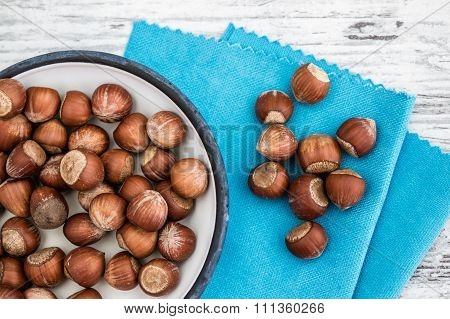 Hazelnuts In Enamel Bowl On A Blue Napkin