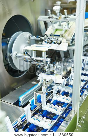 pharmaceutical industry. Line machine conveyer for packaging glass bottles ampoules in boxes at pharmacy industry manufacture factory