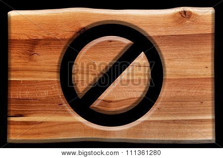 Prohibition, ban or closed symbol cut in wooden board isolated on black. Natural oak wood