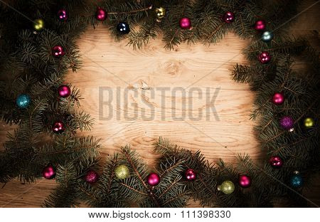 green fir branches on the wooden floor with darkening at the edges with Christmas balls