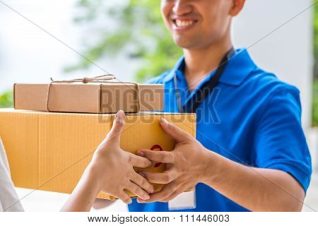 Woman Accepting A Delivery Of Cardboard Boxes From Deliveryman