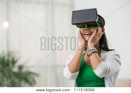 Young woman delighting in virtual reality glasses poster