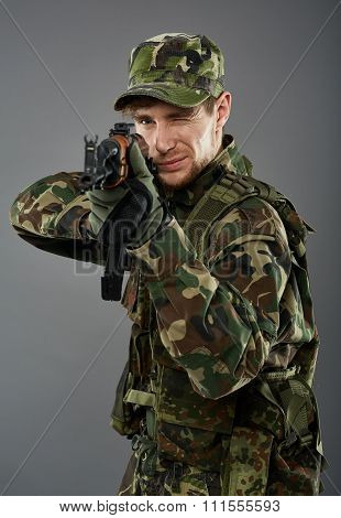 Young soldier with camouflage uniform aiming the target studio shoot poster