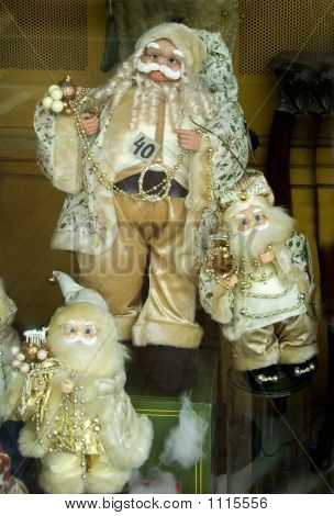 santa claus with two smaller santa claus shown as decoration in a shop.