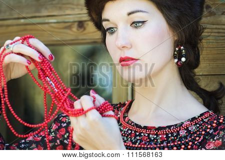 Russian beauty is looking on red coral beads in her raised arms