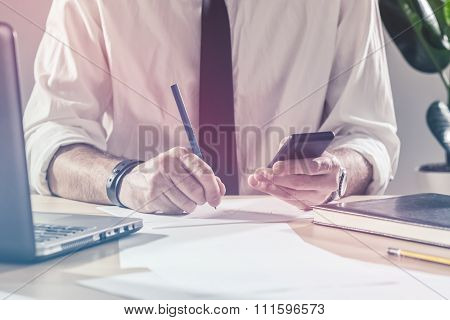 Businessman Writing Notes From Mobile Phone At Office Desk