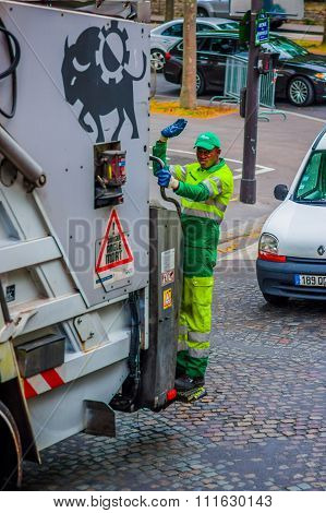 Garbage collector standing on truck, Paris, France