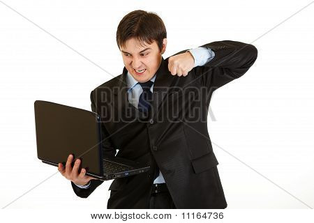 Angry young businessman trying to hit laptop isolated on white