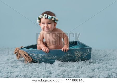 Baby Girl Sitting In A Little Boat