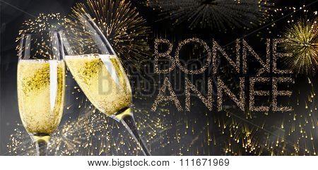 Champagne glasses clinking against glittering bonne annee