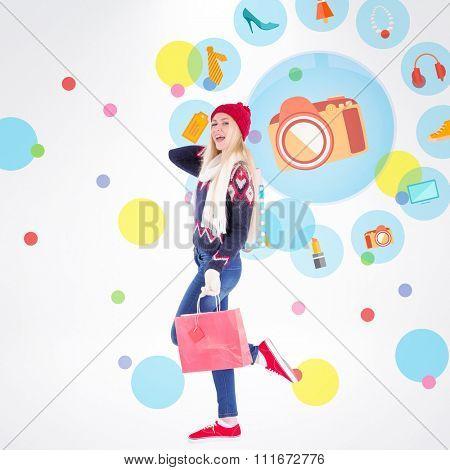 Festive blonde holding shopping bags against dot pattern
