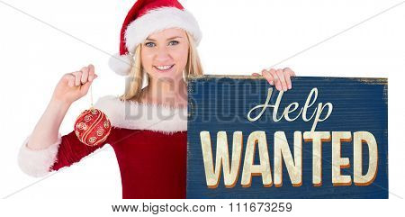Festive cute blonde holding poster and bauble against vintage help wanted sign