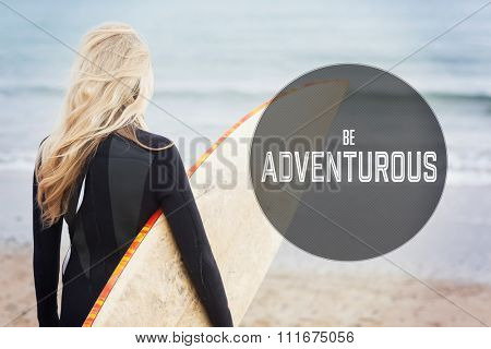 Motivational new years message against rear view of woman in wet suit holding surfboard at beach