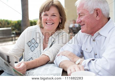 Happy mature senior couple reading a newspaper outside at a cafe