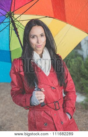 Pretty woman with umbrella standing in the rain