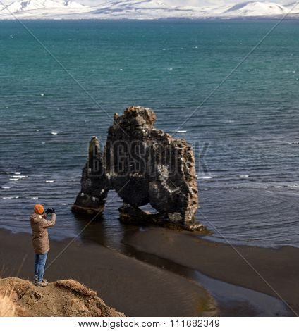 Tourist standing on steep cliff taking a photo of hvitserkur, a natural rock formation along the icelandic coast