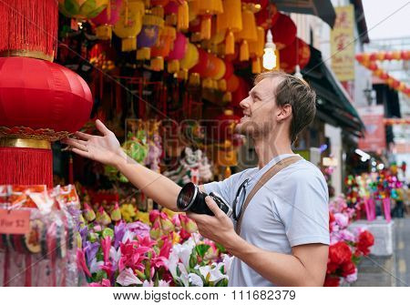 Tourist traveler with camera in modern asian city chinatown shopping looking at a red lantern for souvenir trinkets