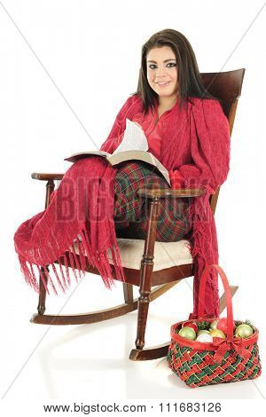 A beautiful teen girl smiling up from reading the Christmas Story.  She's snuggled in her pajamas under a red blanket while sitting in a rocking chair.  On a white background.