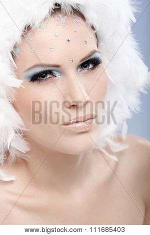 Young winter beauty with a serious look and strasses and white feather hat.