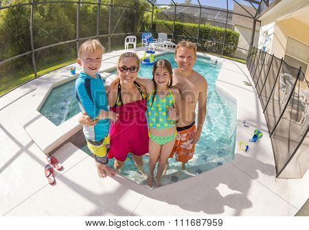 Happy Family playing in a backyard swimming pool