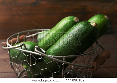 Fresh zucchini in wicker basket on wooden background