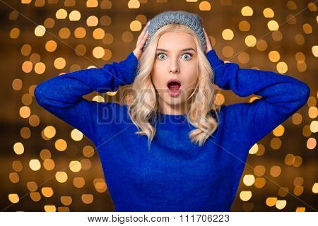 Portrait of a shocked blonde woman standing over holidays lights background