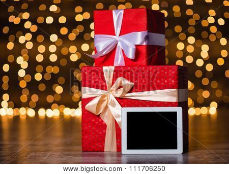 Gift boxes and tablet computer with blank screen standing on the floor over holidays lights background