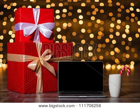 Gift box and laptop computer with blank screen standing on the floor over holidays lights background