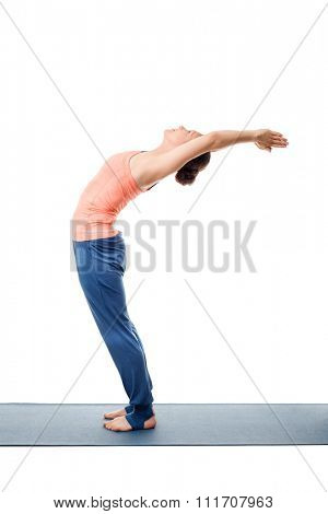 Beautiful sporty fit woman practices Sivananmda yoga asana Anuvittasana  - standing back bend pose isolated on white
