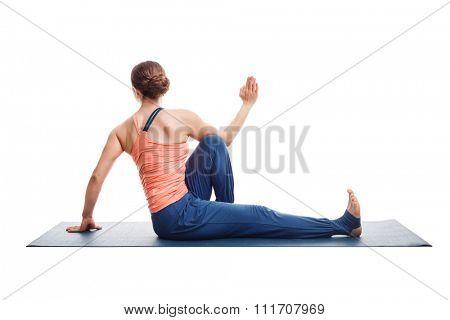 Beautiful sporty fit yogini woman practices yoga asana Marichyasana C - seated spinal twist isolated on white