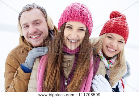 Joyful friends in winterwear looking at camera with smiles outdoors