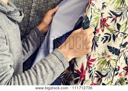 closeup of a young caucasian man looking at some shirts in a clothing rack