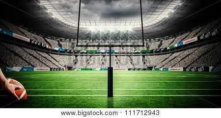 American football player preparing for a drop kick against american football arena