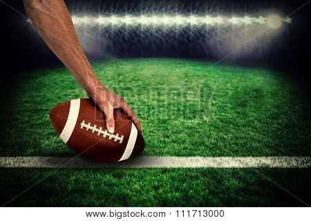 Close-up of American football player placing the ball against rugby pitch