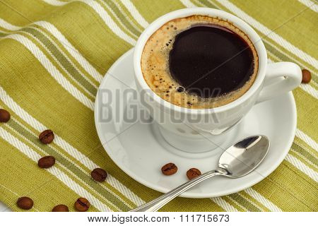 Black coffee in white porcelain cup with saucer and spoon on striped napkin