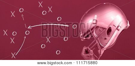 American football player handing his sliver helmet against red background