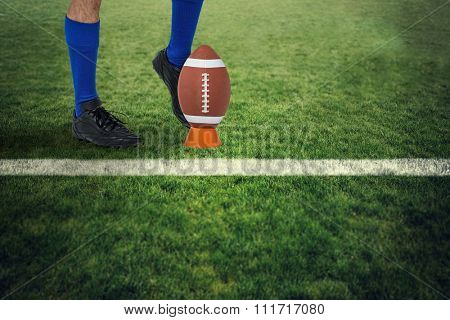 American football player kicking ball against rugby pitch
