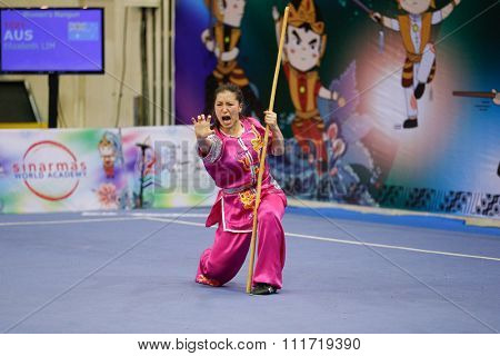 JAKARTA, INDONESIA - NOVEMBER 17, 2015: Elizabeth Lim of Australia performs the movements in the women's Gunshu event at the 13th World Wushu Championship 2015 in Istora Senayan Stadium.