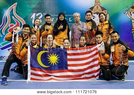 JAKARTA, INDONESIA - NOVEMBER 17, 2015: The Malaysian Wushu taolu athletes show off the medals they won at the 13th World Wushu Championship 2015 held at the Istora Senayan Stadium.
