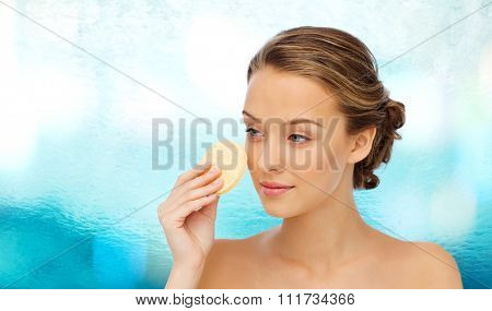 beauty, people and skincare concept - young woman cleaning face with exfoliating sponge over blue water background