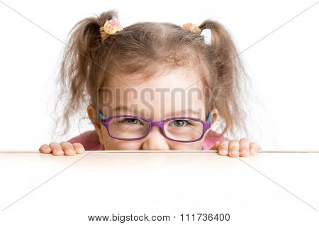 frightened kid in spectacles looking from under table desk