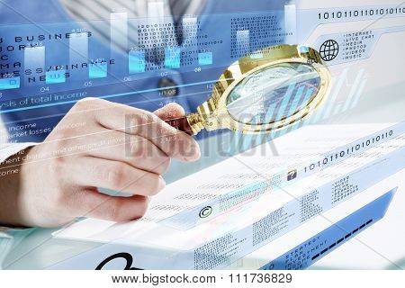 Close up of business person investigating infographs with magnifier