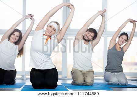 Fitness stretching practice group of four beautiful happy fit young people working out in sports club doing side bend exercises with raised arms on blue mats in class poster