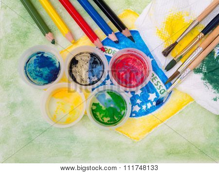 Paints Lids,brushes, Pencils And Stained Fabric On The Brazil Flag Watercolor Painting