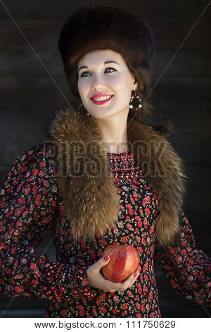 Russian fashion style portrait of young smiling woman with red apple