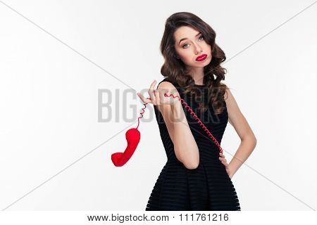 Bored tired beautiful curly young woman with bright makeup in retro style in black dress with red telephone receiver over white background